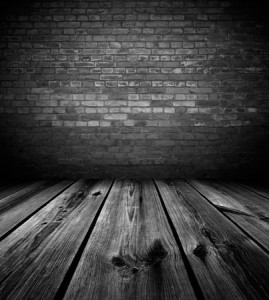 Photo of a dark and empty room, old wooden planks on the floor, old, dark brick wall blocks the way out.